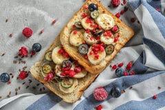 Smakelijke zoete toosts met verse banaan en bessen op lijst royalty-vrije stock afbeelding