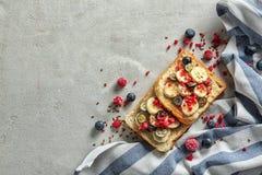 Smakelijke zoete toosts met verse banaan en bessen op lijst stock afbeeldingen