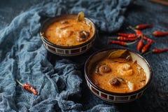 Smaklig asiatisk soppatom sötpotatis i små bunkar med chilipeppar, räka, champinjoner, kokosnöten och limefrukt på en mörk bakgru arkivbild