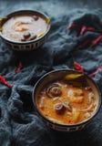 Smaklig asiatisk soppatom sötpotatis i små bunkar med chilipeppar, räka, champinjoner, kokosnöten och limefrukt på en mörk bakgru arkivfoto