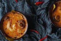 Smaklig asiatisk soppatom sötpotatis i små bunkar med chilipeppar, räka, champinjoner, kokosnöten och limefrukt på en mörk bakgru royaltyfri fotografi