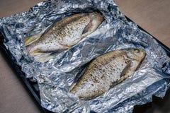 Smaklig bakad fisk i folie på tabellnärbild arkivfoto