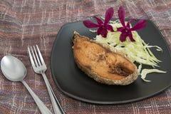 Smaklig bakad fisk på den isolerade plattan arkivbild