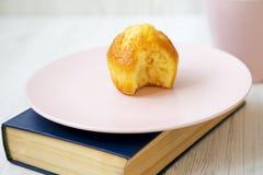 Smaklig biten muffin på en blå bok, sidosikt arkivbild