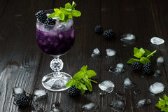 Smaklig björnbärcoctail i vinexponeringsglas med mintkaramellen och is på den mörka trätabellen Sommarbärlemonad Arkivbild