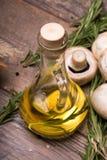 Smaklig doftande solrosolja för sallader på en träbakgrund Några filialer av rosmarin och champinjoner på ett skrivbord Royaltyfria Foton