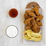 Smaklig fastfood: stekt kycklingtrumpinnar, kryddiga vingar, pommes frites och fega remsor, kallt ?l och sur-s?tsak s?s ?ver vit arkivfoton