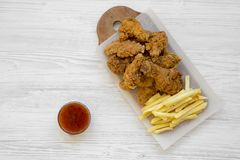 Smaklig fastfood: stekt kycklingtrumpinnar, kryddiga vingar, pommes frites och fega remsor med sur-sötsak sås över vit träsur arkivbild