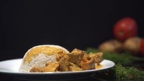 Smaklig feg curry, Inadian maträtt med ångade ris Kock som tillfogar feg curry till de ångade risen, platta på svarten stock video