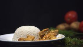 Smaklig feg curry, indisk maträtt med ångade ris Kock som tillfogar feg curry till de ångade risen, platta på svarten stock video