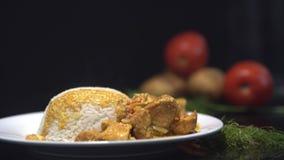 Smaklig feg curry, indisk maträtt med ångade ris Kock som tillfogar feg curry till de ångade risen, platta på svarten arkivfilmer