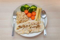 Smaklig fiskfilébiff med ångade grönsaker och råriers royaltyfri foto