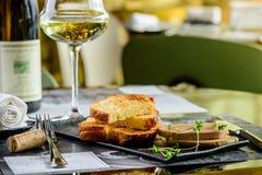 Smaklig foie Gras med rostade bröd och exponeringsglas av vitt vin på en restaur royaltyfria bilder