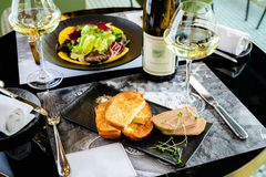 Smaklig foie Gras med rostade bröd och exponeringsglas av vitt vin på en restaur fotografering för bildbyråer