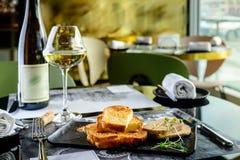 Smaklig foie Gras med rostade bröd och exponeringsglas av vitt vin på en restaur arkivbilder