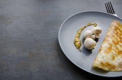 Smaklig frukost, omelett och nya mushooms på plattan, svart bakgrund royaltyfri foto