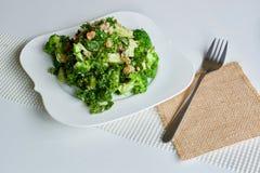 Smaklig grön broccolisallad på den vita plattan arkivbilder