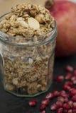 Smaklig Granola i en krus med mandlar och granatäpplet Arkivfoto
