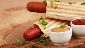 Smaklig grillad fransk varmkorv två med senap och ketchup på tappningskärbräda lager videofilmer