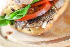 Smaklig grisköttbiffsmörgås i en ciabatta med tomater, grönsallat Arkivfoton