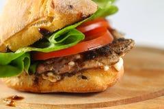 Smaklig grisköttbiffsmörgås i en ciabatta med tomater, grönsallat Arkivbilder