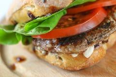 Smaklig grisköttbiffsmörgås i en ciabatta med tomater, grönsallat Fotografering för Bildbyråer