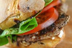 Smaklig grisköttbiffsmörgås i en ciabatta med tomater, grönsallat Arkivbild