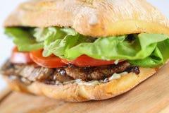 Smaklig grisköttbiffsmörgås i en ciabatta med tomater, grönsallat Royaltyfria Bilder