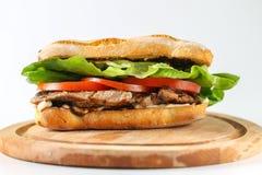 Smaklig grisköttbiffsmörgås i en ciabatta med tomater, grönsallat Royaltyfri Foto