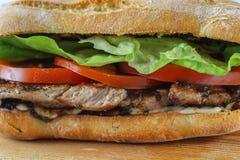 Smaklig grisköttbiffsmörgås i en ciabatta med tomater, grönsallat Royaltyfria Foton