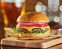 Smaklig hamburgare för snabbmatstilost med öl arkivbild