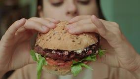 Smaklig hamburgare i händer av flickan lager videofilmer
