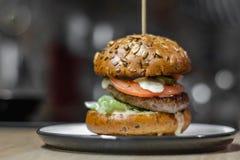 Smaklig hamburgare med grillad nötkött, grönsallat och majonnäs som tjänas som på den keramiska plattan på vanligt ljust kök, slu royaltyfria bilder