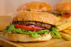 Smaklig hamburgare med smältt ost och tjockt Royaltyfri Fotografi