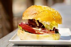 Smaklig hamburgare med smältt ost och tjockt Royaltyfri Bild