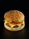 Smaklig hamburgare på svart bakgrund Royaltyfri Foto