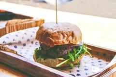 Smaklig hamburgare på träbräde Arkivfoto