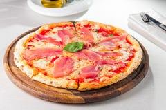 Smaklig hel italiensk pizza som överträffas med tunt skivad prosciuttoskinka Fotografering för Bildbyråer