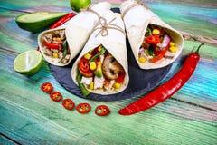 Smaklig hemlagad burrito med grönsaker och nötkött med röd kryddig peppar på ett skifferbräde Mexicansk burritoscloseup fotografering för bildbyråer