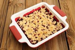 Smaklig hemlagad körsbärsröd havresmulpaj i fyrkantig vit bakningmaträtt på Royaltyfri Foto