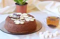 Smaklig kaka med chokladfjärilen och blommor på den bruna plattan Arkivbilder