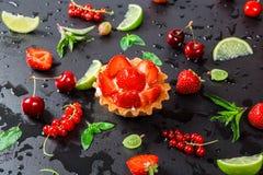 Smaklig kakakorg med jordgubbar och kräm på en svart bakgrund med bärvinbär, krusbär, körsbär, limefruktskivor och Arkivbilder