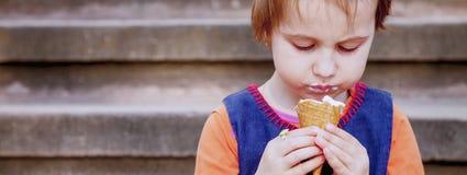smaklig kräm- is Gullig flicka för litet barn som utomhus äter glass Mat efterrätt, lyckligt barndombegrepp arkivfoto