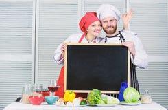 Smaklig laga mat grupp Par av mannen och kvinnan som ger det ok tecknet p? svart tavla, i att laga mat skola Ledar- kock och f?rb royaltyfria bilder