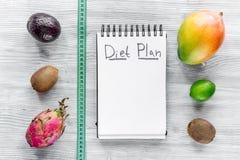 Smaklig mat för att banta Anteckningsboken för bantar upp plan och frukter på grå träåtlöje för bästa sikt för tabell arkivbilder