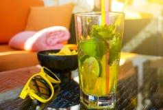 Smaklig mojito på trätabellen med gul solglasögon på gatakafét, begrepp för sommarsemester Sommar dricker begrepp royaltyfria bilder