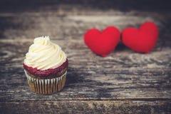 Smaklig muffin med två röda hjärtor på träbakgrund Royaltyfri Bild