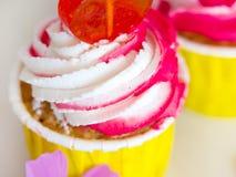 Smaklig muffincloseup med vit och rosa kr?m royaltyfri fotografi