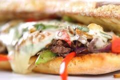 Smaklig nötköttbiffsmörgås med lökar, champinjonen och smältt provoloneost Fotografering för Bildbyråer