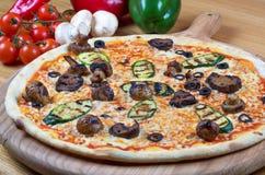 Smaklig ny pizza dekorerade med champinjoner och zucchinin på träbakgrund Fotografering för Bildbyråer